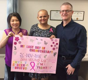 Prof Chan with patient Katherine and Dr Willsher with Katherine's poster celebrating her last day of chemo